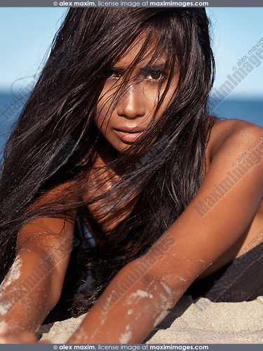 Beautiful young woman with wet long hair lying in the sand at the beach, artistic portrait