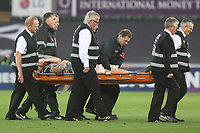 Dan Baker of Ospreys is stretchered off by physics after landing on his ankle after an in the air tackle from Fritz Lee of Clermont during the Champions Cup Round 1 match between Ospreys and Clermont at The Liberty Stadium, Swansea, Wales, UK. Sunday 15 October 2017