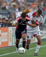 Second half substitute New England Revolution midfielder Benny Feilhaber (22) brings the ball forward as DC United defender Perry Kitchen (23) defends. In a Major League Soccer (MLS) match, DC United defeated the New England Revolution, 2-1, at Gillette Stadium on April 14, 2012.