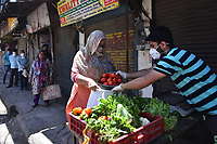 NEW DELHI, INDIA - APRIL 3: A woman shops from a vegetable vendor s stall while other people maintain social distance, on day ten of the 21 day nationwide lockdown to check the spread of coronavirus, at Moti Nagar in New Delhi, India, on Friday, April 3, 2020.  <br /> Photo Imago/Panoramic/Insidefoto