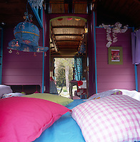 A vintage steel Airstream trailer is decorated in a bold vibrant style. The bedroom area is painted pink and cushions are scattered around.