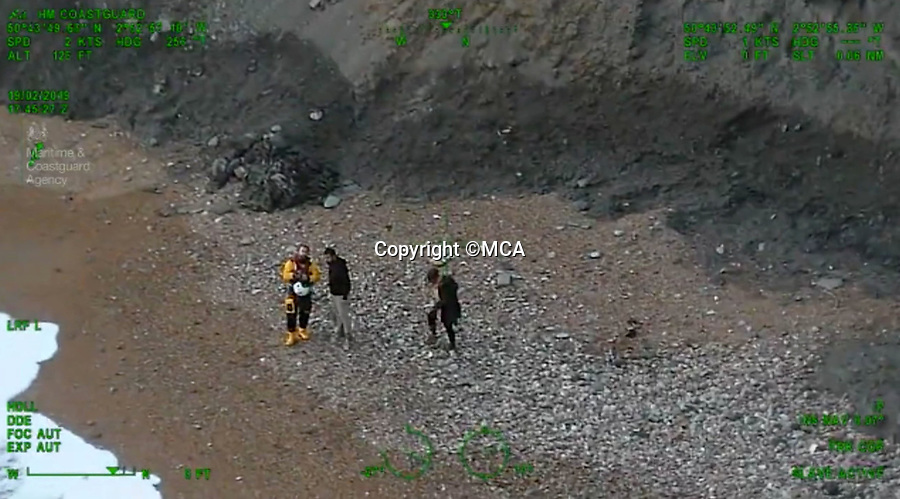BNPS.co.uk (01202 558833)Pic:  MCA/BNPS<br /> <br /> The stranded couple with a member of the coastguard, being prepared to be plucked to safety.<br /> <br /> This is the heart-stopping moment two walkers were saved from drowning after being cut off by the tide.<br /> <br /> Dramatic video footage from a coastguard helicopter shows the strong waves of the incoming tide licking at the feet of the young couple.<br /> <br /> They were rescued in the nick of time by a coastguard winchman who plucked them off the beach at Charmouth, Dorset.
