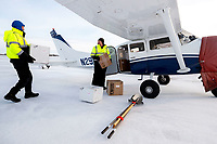Chief pilot Russ Dunlap (Left) helps volunteer pilot Mike Swalling load his Cessna 206 with supplies headed to Nulato at the Galena airport during the 2017 Iditarod on Thursday afternoon March 9, 2017.<br /> <br /> Photo by Jeff Schultz/SchultzPhoto.com  (C) 2017  ALL RIGHTS RESERVED