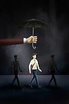 Illustrative image of hand holding an umbrella above businessman representing life insurance