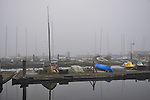 Dry docked sailboats and canoes wrapped in early morning fog