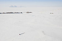 A team runs on the trail between Unalakleet and Shaktoolik with the frozen Norton Sound and Besboro Island in the background during the 2010 Iditarod