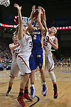 SIOUX FALLS, SD - MARCH 10: Macy Miller #12 from South Dakota State University takes the ball to the basket between Margaret McCloud #30 and Kelly Stewart #15 from the University of South Dakota in the first half of the Summit League Championship Tournament game Tuesday at the Denny Sanford Premier Center in Sioux Falls, SD. (Photo by Dick Carlson/Inertia)