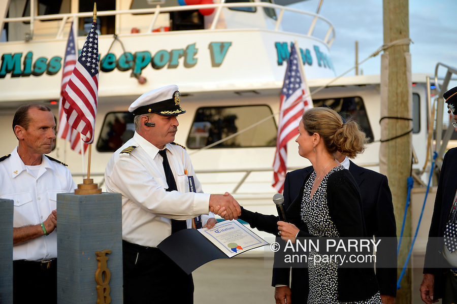 Freeport, New York, USA. September 10, 2014. Nassau County Legislator LAURA CURRAN (D-Baldwin) shakes hands with Captain FRANK RIZZO and hands him a Citation honoring him, at a dockside remembrance ceremony in honor of victims of the terrorist attacks of September 11 2001, at the boat Miss Freeport V, on Freeport's Nautical Mile. Further ceremonies were held on board the vessel, which Capt. Rizzo, a host of the event, sailed from the Woodcleft Canal on the South Shore of Long Island, on the eve of the 13th Anniversary of the 9/11 attacks.
