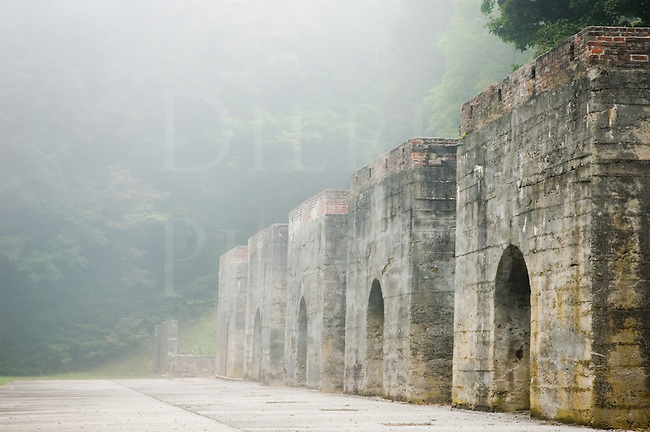 Coming out of a summer morning fog, these old lime kilns appear like the walls of a medieval castle but are only the ruins of a large industrial lime making site that closed over a hundred years ago. All of the lime produced here was made from limestone harvested in a large underground mine and was taken by rail to be used in making iron and steel in Pittsburgh, Johnstown, and other steel towns. The other main use of lime that continues to this day is in agriculture where it is spread onto fields, and it has many other industrial uses as well. The furnaces were heated with coal, also brought by rail.<br />