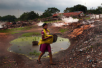 A girl walks through an area at Ghannodi where poisionous gases and fumes spew from the ground caused by burning coal seams beneath the surface. A huge coal mine fire is engulfing the city of Jharia from all its sides. All scientific efforts have gone in vain to stop this raging fire. This fire is affecting lives of people living in and around Jharia. Jharkhand, India. Arindam Mukherjee