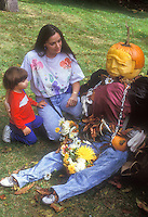 Carved pumpkin person, dressed in clothing and with flowers, with woman and child son boy toddler