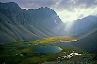 Sunlight spills from behind clouds into unnamed valley amid rugged peaks of the Endicott Mountains in the Brooks Range at Gates of Arctic National Park, Alaska, TomBean_Pix_0735.