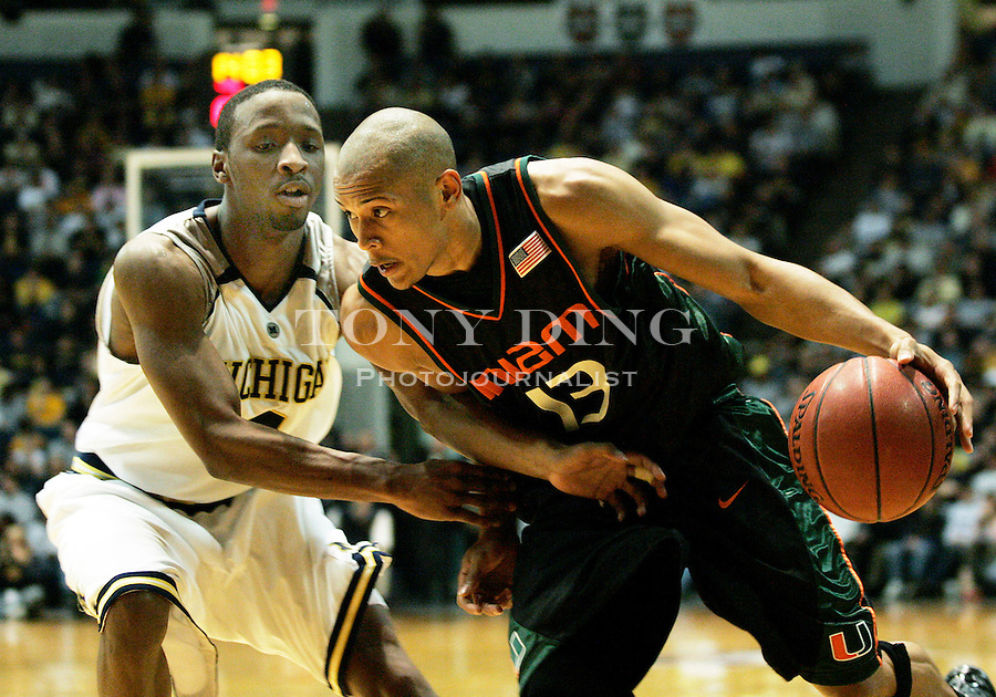 Michigan guard Daniel Horton (left) defends against Miami guard Guillermo Diaz (13) during the second half of a quarterfinals round game of the NIT basketball tournament Wednesday, March 22, 2006, in Ann Arbor, Mich. Michigan won 71-65. (AP Photo/Tony Ding)