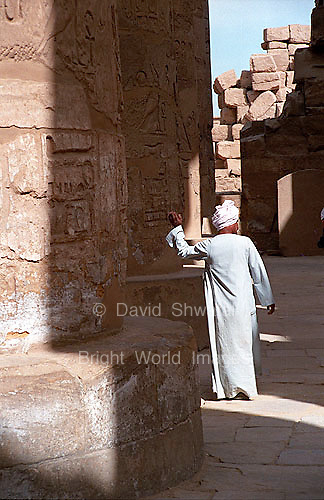 Egyptian man stands amid Columns in Karnak Temple in Luxor, Egypt..