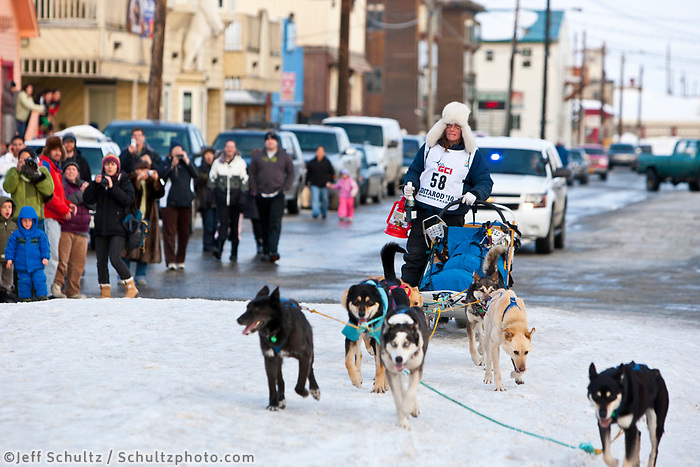 Rookie musher and red lantern award winner Celeste Davis runs up the finish chute holding her red lantern at Nome during the 2010 Iditarod