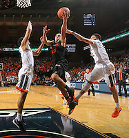 Miami guard Angel Rodriguez (13) shoots between Virginia guard Darius Thompson (51) and Virginia guard Malcolm Brogdon (15) during the game Tuesday, Jan. 12, 2016 in Charlottesville, Va. Virginia defeated Miami 66-58. Photo/Andrew Shurtleff