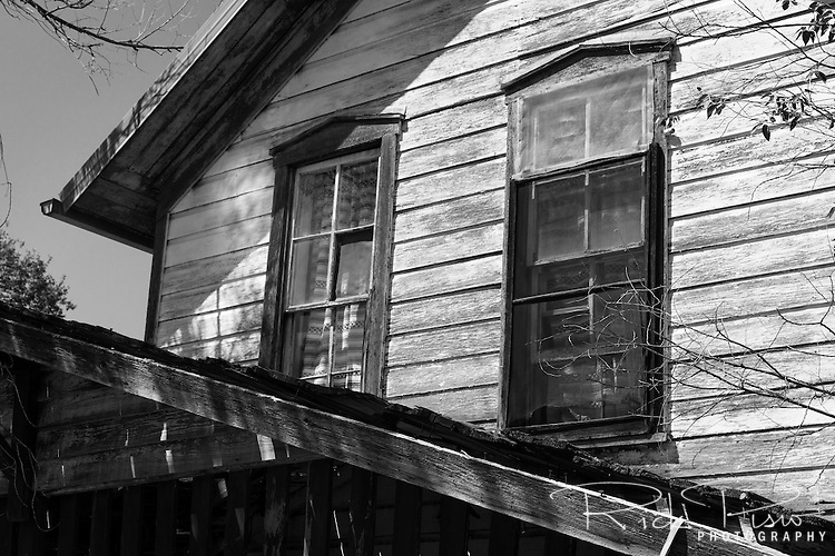 Upstair windows on a weathered home in Madrid, New Mexico.