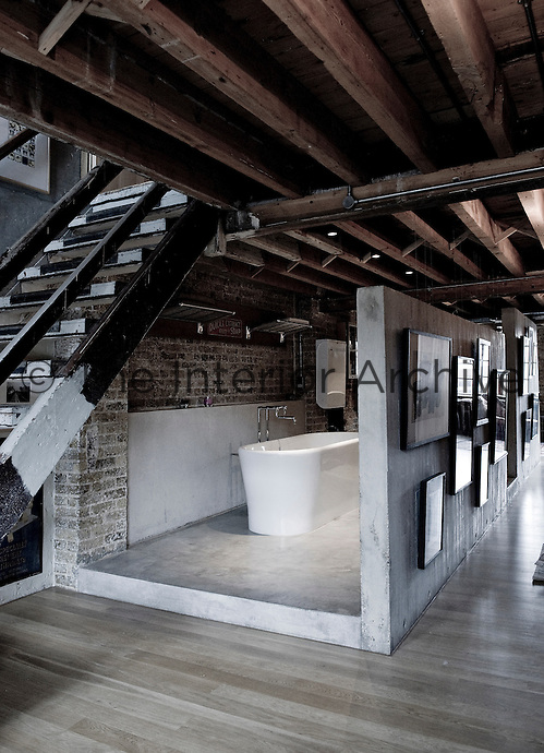 A free-standing contemporary bath is partially concealed behind a concrete partition wall displaying a collection of artwork