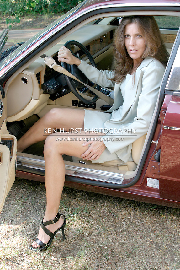 Sexy, attractive brunette woman getting out or getting in an elegant luxury car.