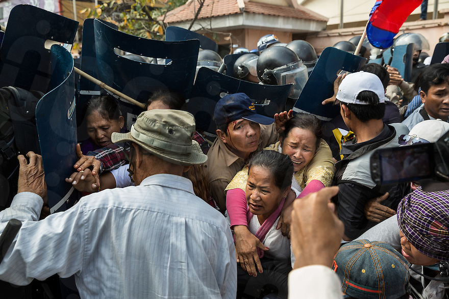 January 27, 2014 - Phnom Penh, Cambodia. People surround Mam Sonando (not pictured) as riot police storm a protest. Sonando and supporters gathered in front of the Ministry of Information to ask for a T.V. station and wider bandwidth for his Beehive radio station. © Nicolas Axelrod / Ruom Collective