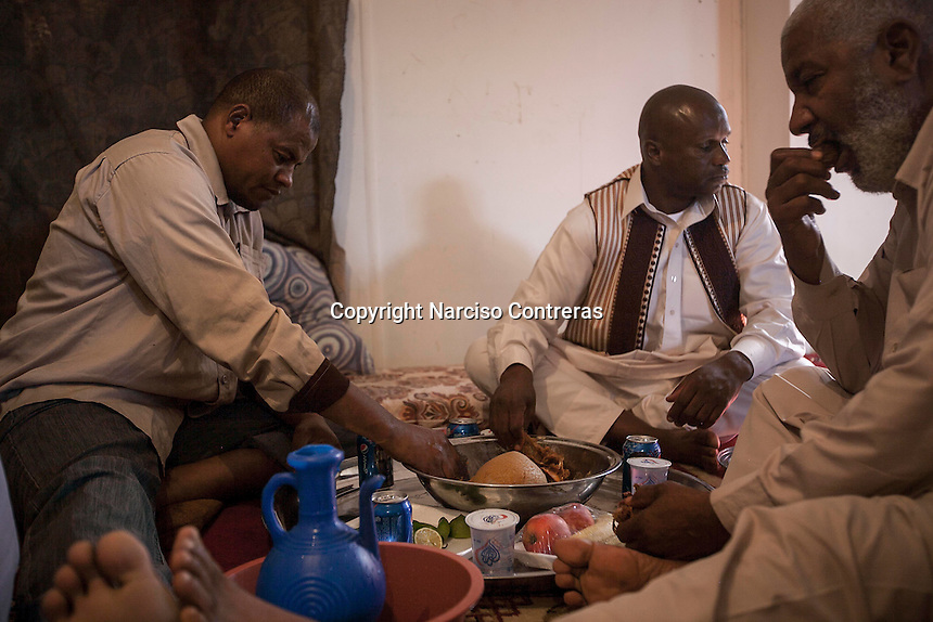 November 13, 2014 - Tripoli City, Libya: Tawerghans men gather for a lunch meal as they attend a wedding celebrated in a construction site in the Fallah road of Tripoli used as a temporary shelter after the Tawerghans were forced to move from their city home in southeast of Misrata as they were harassed by the armed militias of Misrata during the 2011 uprising against Colonel Gaddafi. (Photo/Narciso Contreras)