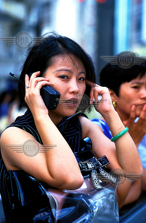 Mark Henley/Panos Pictures..China, Shanghai..Young woman using mobile phone, with her Moschino bag.