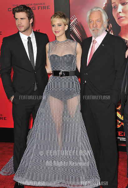 Jennifer Lawrence with Liam Hemsworth (left) &amp; Donald Sutherland at the US premiere of their movie &quot;The Hunger Games: Catching Fire&quot; at the Nokia Theatre LA Live.<br /> November 18, 2013  Los Angeles, CA<br /> Picture: Paul Smith / Featureflash