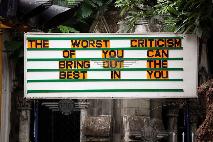 A sign reads 'The worst criticism of you can bring out the best in you.'