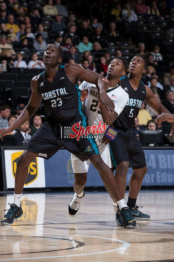Badou Diagne (23) and Jaylen Shaw (5) of the Coastal Carolina Chanticleers box out Cornelius Hudson (25) of the Wake Forest Demon Deacons during first half action at the LJVM Coliseum on December 18, 2015 in Winston-Salem, North Carolina.  The Demon Deacons defeated the Chanticleers 83-77.  (Brian Westerholt/Sports On Film)