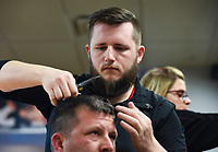 """Stylist Jon Danger (top) gives a haircut to Nick Willbanks of Fayetteville (bottom), Monday, March 23, 2020 at Sports Clips Haircuts in Fayetteville. Check out nwaonline.com/200323Daily/ for today's photo gallery.<br /> (NWA Democrat-Gazette/Charlie Kaijo)<br /> <br /> Monday is the last day that hair salons, tattoo shops, nail salons and massage parlors are permitted to stay open. He said he heard the news while watching Gov. Asa Hutchinson's address to the state. <br /> <br /> """"[It] sucks man. My job and security. Still got bills to pay. [It's] the unknown of when we're coming back. I'm on a weird fence of do I need a job? Or do I want people to die?"""" he said."""