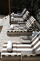 Natural wood weathers to a soft grey in the strong southern Spanish sun softening a terrace deck and four poolside lounge chairs.