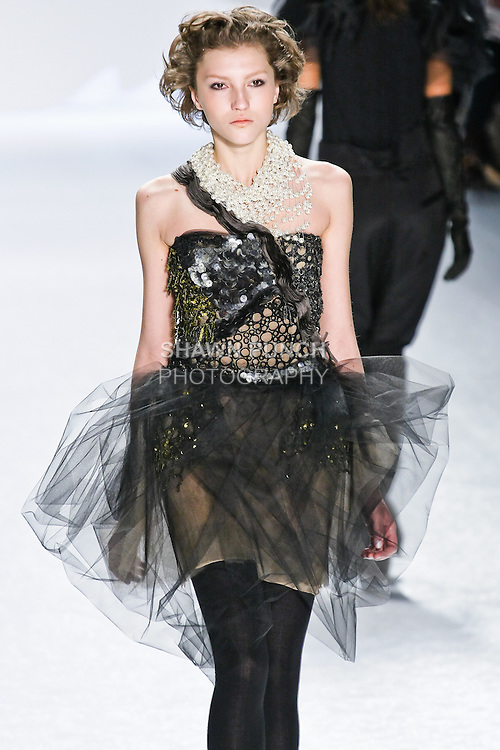 Ursula Konina walks runway in a charcoal, olive. black. and silver distressed sequin and tulle one shoulder bustier dress with swagged black tulle skirt at  the Vera Wang Fall 2010 fashion show during Mercedes-Benz Fashion Week.