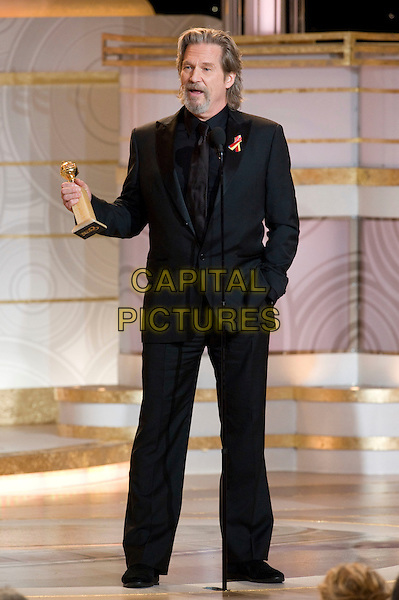 "JEFF BRIDGES .Accepts the Golden Globe Award for BEST PERFORMANCE BY AN ACTOR IN A MOTION PICTURE - DRAMA for his role in ""Crazy Heart"" at the 67th Annual Golden Globe Awards at the Beverly Hilton in Beverly Hills, CA, USA..January 17th, 2010.                               .globes stage microphone full length  black suit  award trophy winner goatee facial hair hand in pocket .CAP/AW/HFPA.Supplied by Anita Weber/Capital Pictures"