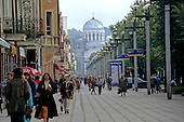 Kaunas, Lithuania. People walking on the street with row of lampposts, the Russian Orthodox Church in the centre.