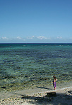 Girl on Caribbean shore looking out over water