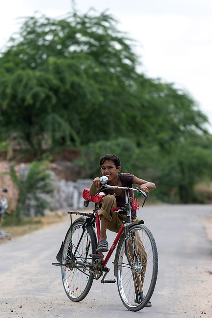 03 September, 2013, Jodhpur, Rajasthan INDIA :  A local boy rides by the road built under the Pradhan Mantri Gram Sadak Yojana program (PMGSY) in Nokda Kidani village in Rajasthan. PMGSY is a nationwide plan in India to provide good all-weather road connectivity to unconnected villages.<br /> It is under the authority of the Ministry of Rural Development and was begun on 25 December 2000 It is fully funded by the central government and implemented in conjunction with the World Bank<br /> The goal was to provide roads to all villages  with a population of 500 persons and above by 2007, in hill states, tribal and desert area villages with a population of 250 persons and above by 2007. Picture by Graham Crouch/World Bank
