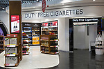 Inside the Duty Free shopping area at Stansted airport showing the screened off section for duty free cigarettes and display of bottles of alcohol