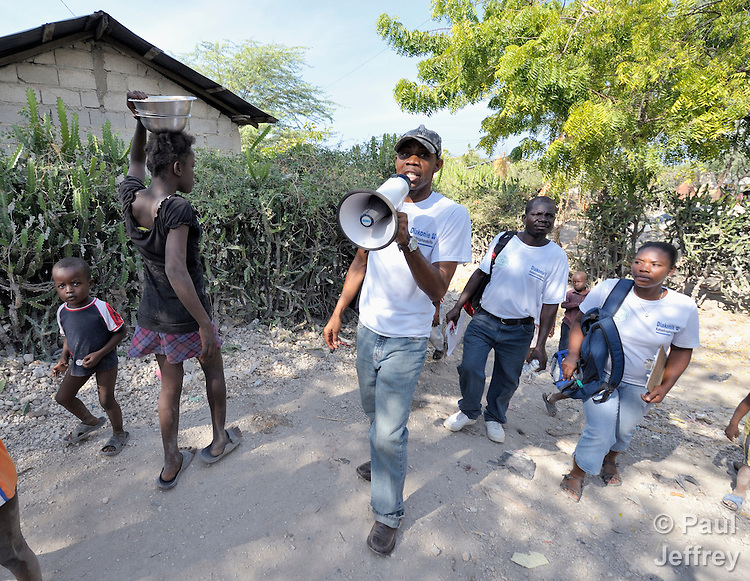 Prelok Pierre Louis (with megaphone), a community health worker for Oganizasyon Sante Popil (OSAPO), speaks to residents of Montrouis, Haiti, about steps they can take to prevent the spread of cholera, which appeared on the quake-ravaged Caribbean island nation in late 2010. OSAPO's work is supported by Diakonie Katastrophenhilfe and the Lutheran World Federation, both members of the ACT Alliance. Health workers from OSAPO go out to surrounding neighborhoods and communities in teams of three, providing education, distributing anti-bacterial soap and oral rehydration salts, and referring ill patients to the OSAPO clinic...