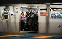 Passengers crowd into a packed E train in the New York subway in the borough of Queens on Saturday, September 29, 2012. Service disruptions caused by a switch problem caused riders to seek alternative routes. (© Richard B. Levine)