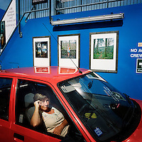 A woman sits in her car on the ferry transporting people from Truro to St Just, Cornwall, next to framed photographs on the side of the ferry.