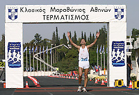 02 NOV 2003 -  ATHENS, GREECE - Nicos Polias (GRE) crosses the Athens Classic Marathon finish line in the Kallimarmaro Stadium. (PHOTO (C) NIGEL FARROW)