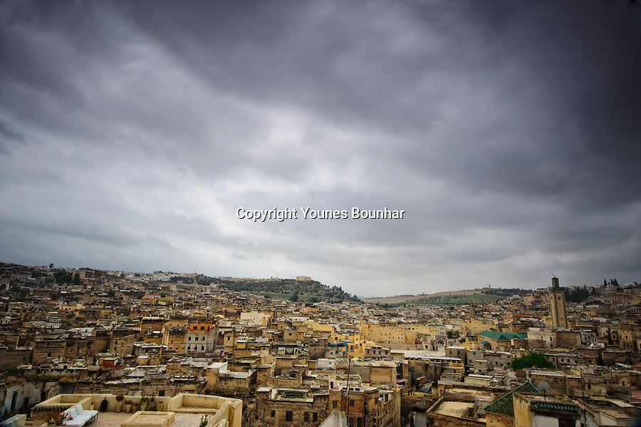 Rooftop view overlooking the medieval city of Fes under cloudy and menacing skies