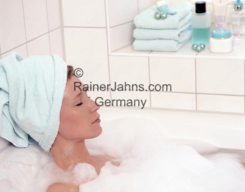 Frau nimmt Schaumbad, entspannt, Augen geschlossen, Handtuch um ihren Kopf gewickelt   woman taking a foam bath, relaxed, eyes closed, towel wrapped around her head