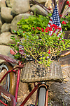 Bicycle with basket of flowers and flag.