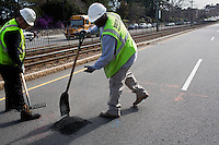 Jerome Whitaker (right) and David Dollosa fill potholes with asphalt while working for the Boston Public Works Department in Boston, Massachusetts, USA, on April 12, 2012. The city uses a computer system to track public complaints and record work done by city crews to mitigate these complaints.  A supervisor or inspector photographs before and after pictures of the work in addition to making notes about the work done.