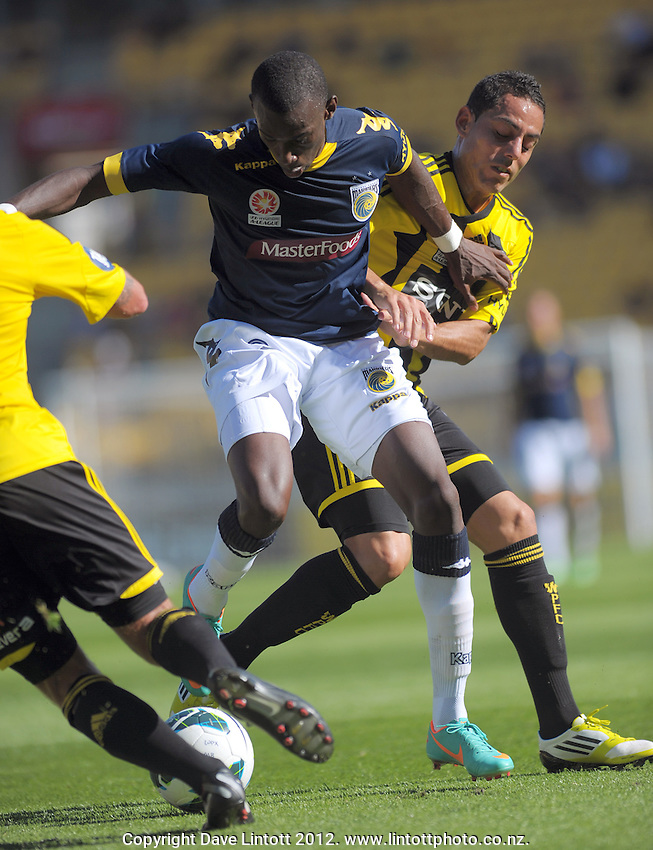 Leo Bertos (right) tries to tackle Bernie Ibini during the A-League football round 12 match between Wellington Phoenix and Central Coast Mariners at Westpac Stadium, Wellington, New Zealand on Saturday, 22 December 2012. Photo: Dave Lintott / lintottphoto.co.nz