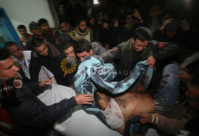 One of two Islamic Jihad militants who were killed in an Israeli airstrike on March 12, 2012 is transported into the morgue of Al-Shifa Hospital in Gaza city, as Israeli warplanes pounded Gaza for a fourth day, killing six more Palestinians which raised the death toll so far to 25, including the two activists who were identified by the Palestinian group as Bassam al-Ajla and Mohammed Dahir. Photo by Mahmud Nassar