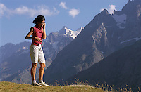 Woman talking on a mobile phone in the middle of a mountain valley.