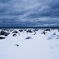 Snow covered rocks on coast, near Kvalness, Lofoten islands, Norway