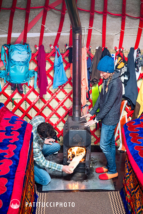 Two people inside a yurt, warming themselves at the fire, while on a ski touring trip in Kyrgyzstan